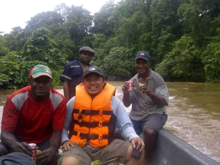 Travelling up river in a small motor boat to reach the village